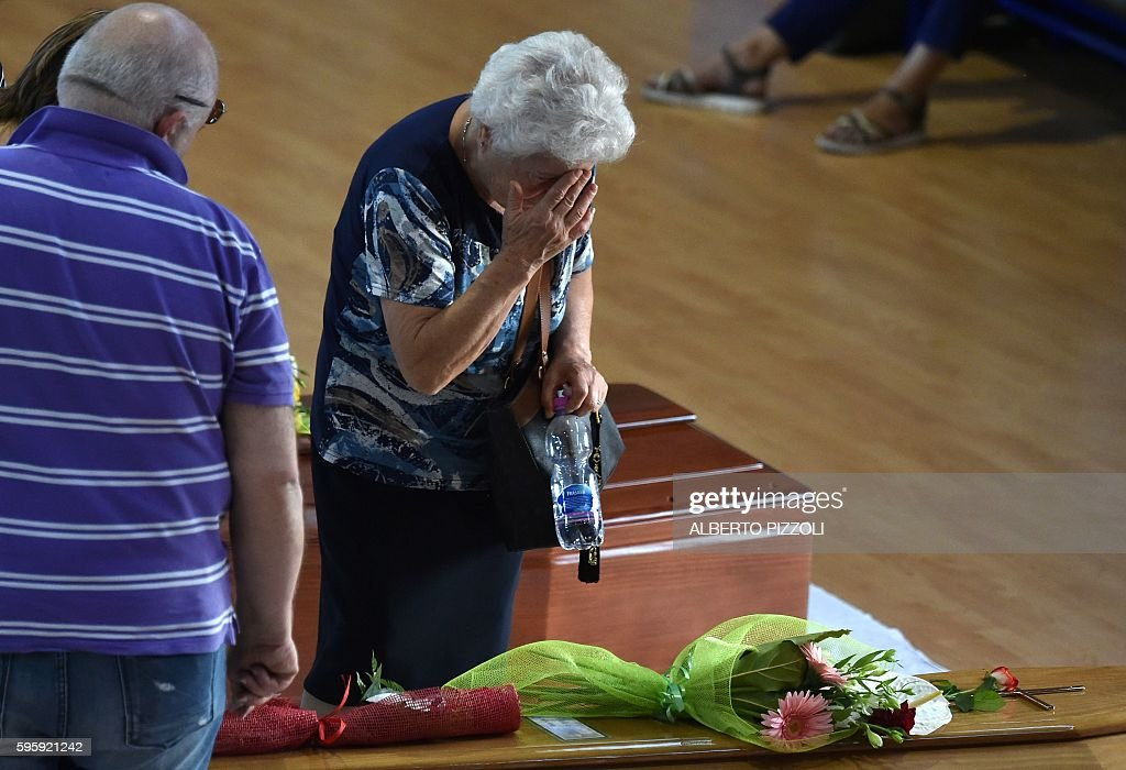A woman mourns next to the coffin of an earthquake victim in a gymnasium arranged in a chapel of rest on August 26 in Ascoli Piceno two day after a...