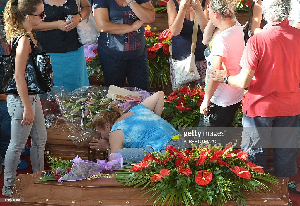 A woman mourns on a coffin, on July 30, 2013, in Moterusciello, southern Italy, during a mass funeral for the 38 people killed in Italy when a coach plunged off a viaduct near Naples. The coach, carrying 48 people including children, rammed several cars after failing to break on a bend, smashing through a crash barrier and off the viaduct to plunge 30 metres (98 feet) down. Prosecutors have launched an investigation into possible manslaughter over the accident, the worst such crash in western Europe in the last decade.