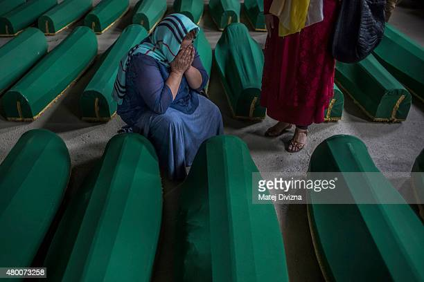 A woman mourns over a coffin among 136 coffins of victims of the 1995 Srebrenica massacre in the hall at the Potocari cemetery and memorial near...