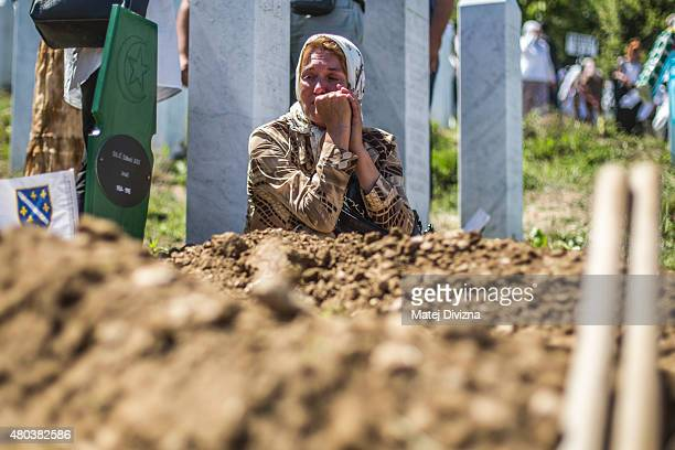 A woman mourns over one of the 136 coffins of newlyidentified victims of the 1995 Srebrenica massacre next to its final grave during the 20th...