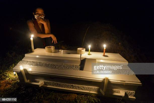A woman mourns over the coffin of a relative killed by a mudslides caused by heavy rains at the cemetery in Mocoa Putumayo department Colombia on...