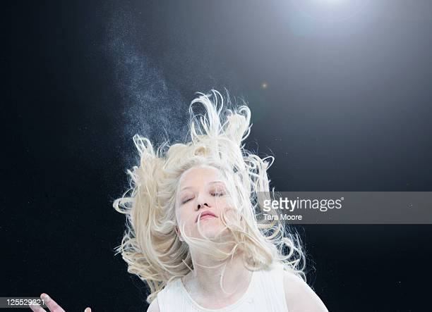 woman moving hair with white dust