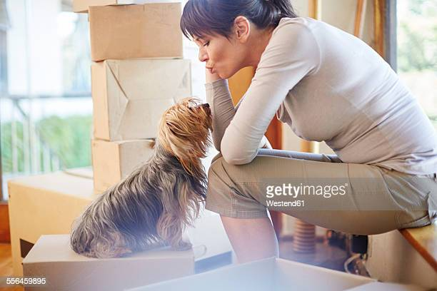 Woman moving house sharing a moment with the dog