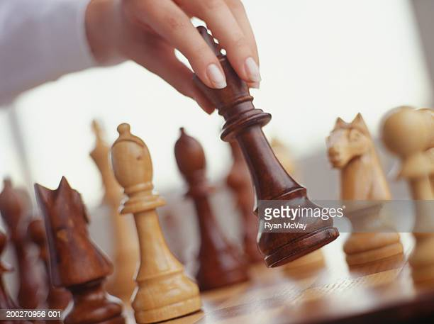 Woman moving king on chessboard, Close-up of hand