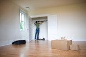 Woman moving shoes into closet of new home