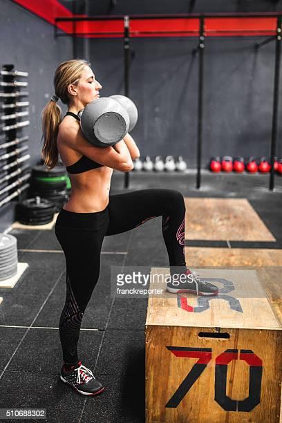 Femme grimper sur la boîte avec Kettlebell