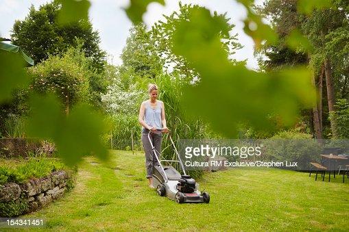 Woman mowing backyard lawn