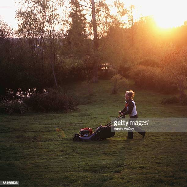 Woman mowing lawn at dawn