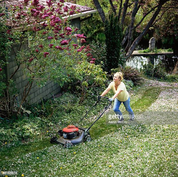 Woman mowing lawn with cherry blossoms