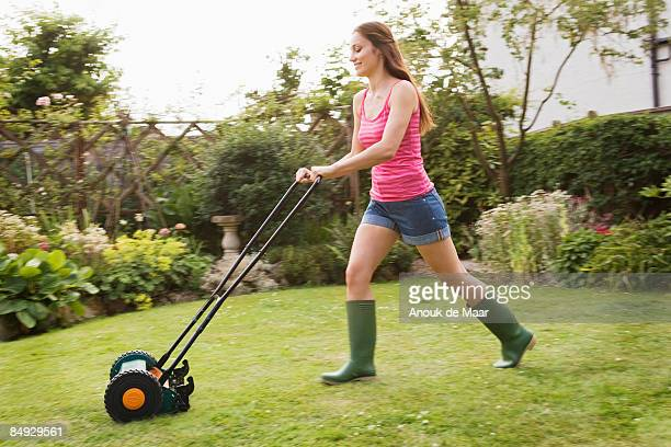 Woman mowing lawn with grass mower