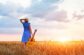 Woman musician with her guitar in the fields looking at sunset, warm summer outdoors
