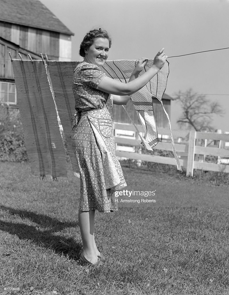 woman n apron smiling at camera as she is hanging laundry on