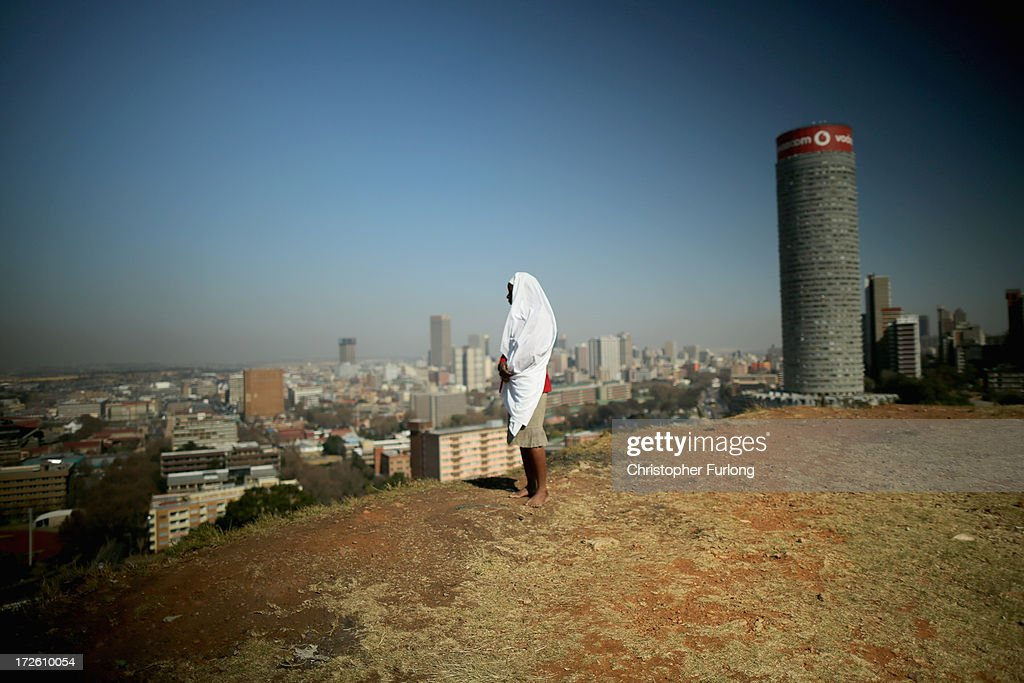 A woman named Pecious overlooks downtown Johannesburg during a prayer service in the Yeoville neighbourhood on July 4, 2013 in Johannesburg, South Africa. The worn, arid space on top of the Yeoville hill offers worshipers of various Christian denominations from South African, Botswana, Zimbabwe, the Democratic Republic of Congo and other African nations an open-air space where they can publicly practice their faith with a scenic view of downtown Johannesburg.