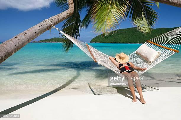 woman napping in hammock at a tropical Caribbean beach