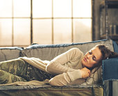 Cat-nap on a sofa. An elegant brunette woman napping on a sofa in a loft, curling her hands under her chin. Urban chic ambiance.