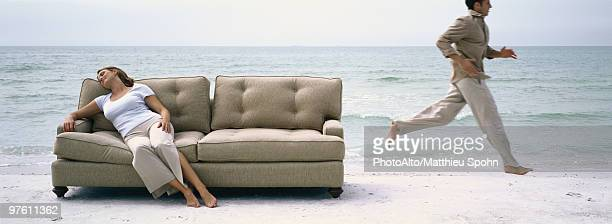 Woman napping on sofa on beach, man running past in background