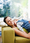 Woman napping on sofa with baby boy