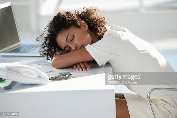 Woman napping with her head resting on desk