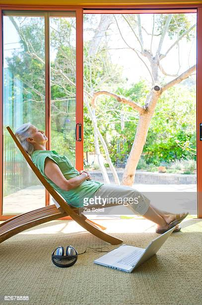woman naps in chair, lapto & headphones nearby