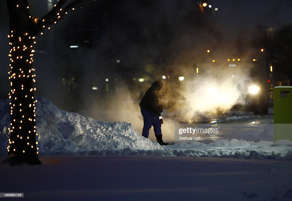 A woman navigates around several inches of snow and steam as the area deals with record breaking freezing weather January 6, 2014 in Detroit, Michigan. Michigan and most of the Midwest received their first major snow storm of 2014 last week and subzero temperatures are expected most of this week with wind-chill driving temperatures down to 50-70 degrees below zero. A 'polar vortex' weather pattern is bringing some of the coldest weather the U.S. has had in almost 20 years.