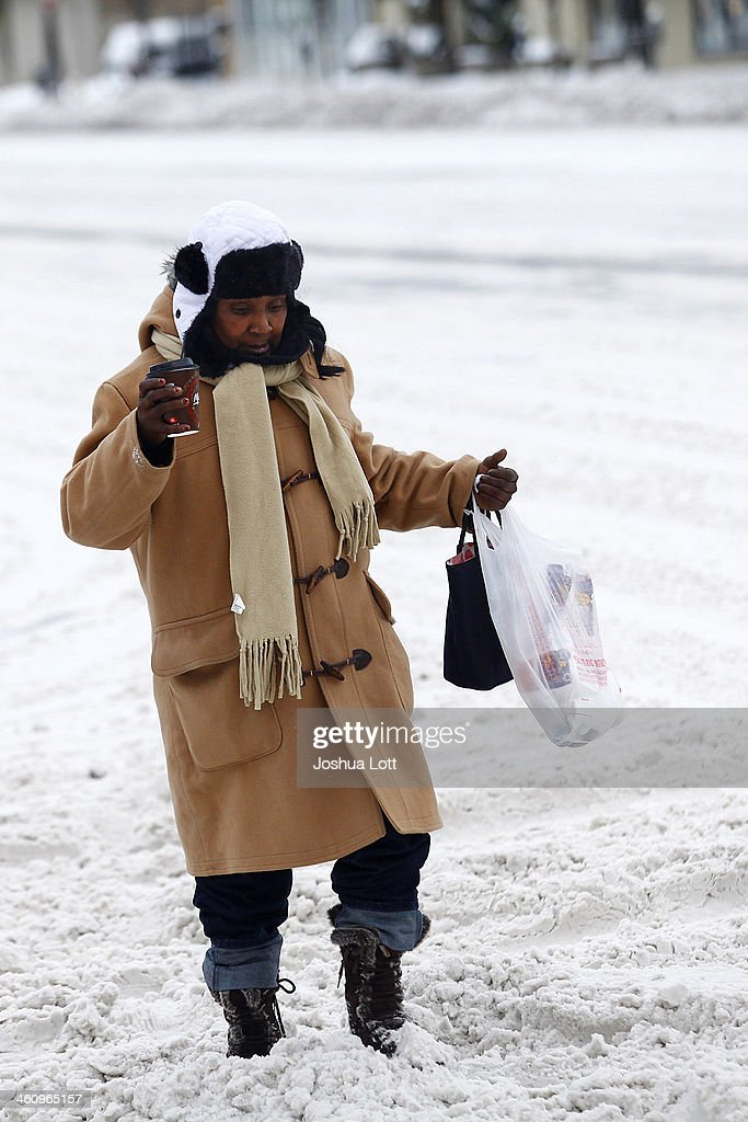 A woman navigates through several inches of snow along Woodward Avenue as the area deals with record breaking freezing weather January 6, 2014 in Detroit, Michigan. Michigan and most of the Midwest received their first major snow storm of 2014 last week and subzero temperatures are expected most of this week with wind-chill driving temperatures down to 50-70 degrees below zero. A 'polar vortex' weather pattern is bringing some of the coldest weather the U.S. has had in almost 20 years.