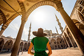 Young woman traveler in black hat and green dress looking on amazing Blue Mosque in Istanbul, Turkey
