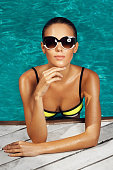 woman near the pool, wearing glasses and swimsuit, tans and relaxing on vacation, healthy athletic body