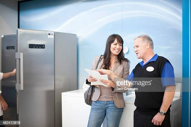 Woman negotiating with salesman in showroom