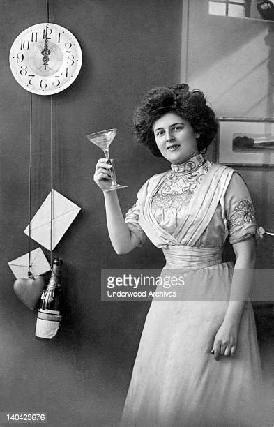 A woman next to a clock with a stone heart and a champagne bottle for pendelum weights raises a champagne glass in a toast at midnight Denmark 1912