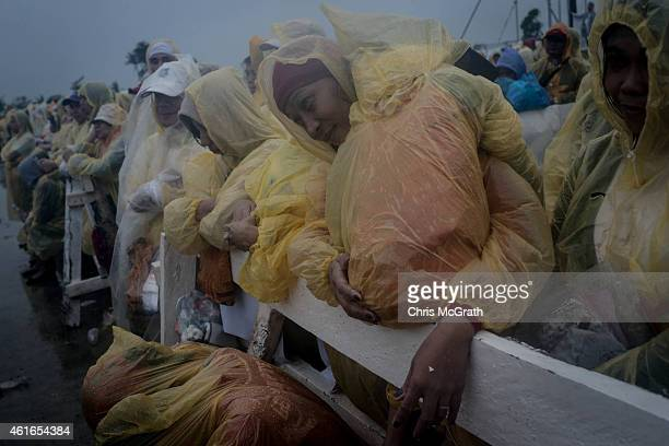 A woman nurses her child as she listens to the mass conducted by Pope Francis at the Tacloban Airport on January 17 2015 in Tacloban Leyte...