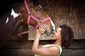 Woman nuzzles a horse.