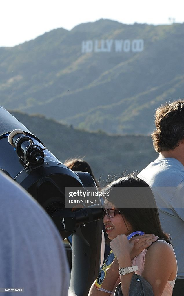 A woman observes the transit of the planet Venus acress the face of the sun from one of the many telescopes set up outside Griffith Observatory in...
