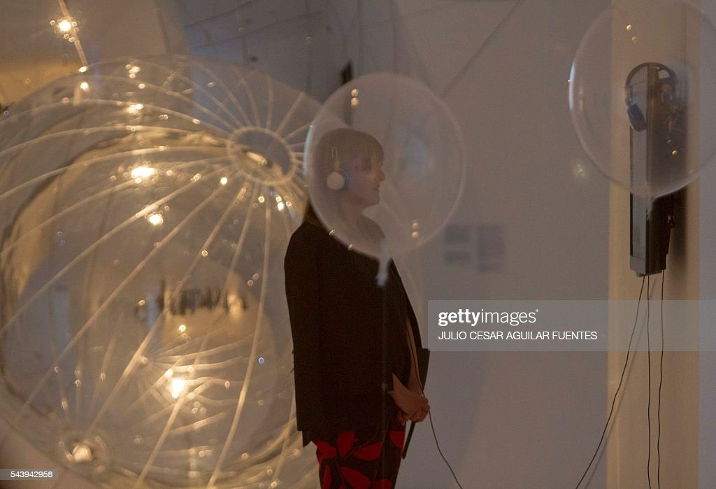 A woman observes the work of the first large exhibition in Latin America of Argentinian artist Tomas Saraceno, called 'One hundred sixty-three thousand light years', in the Museum of Contemporary Art in Monterrey, Nuevo Leon, Mexico, on June 30, 2016. / AFP / Julio Cesar Aguilar Fuentes
