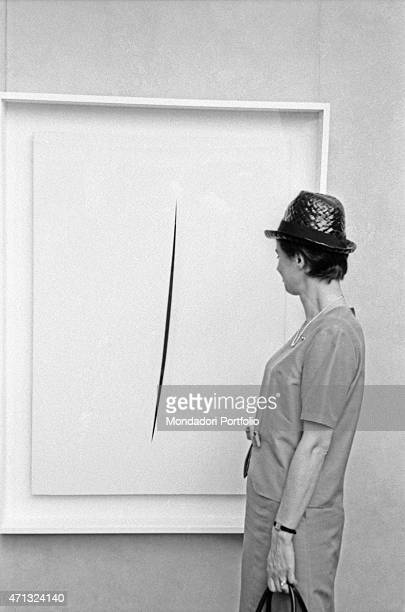 A woman observing a Concetto Spaziale by Lucio Fontana at the 32nd Art Biennale Venice June 1964