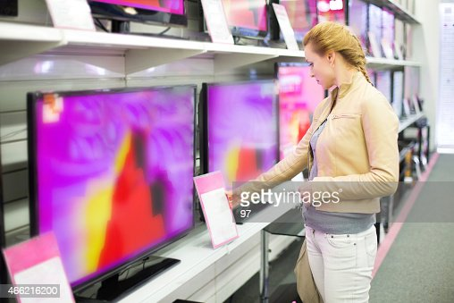 A woman observing prices for a television in a store