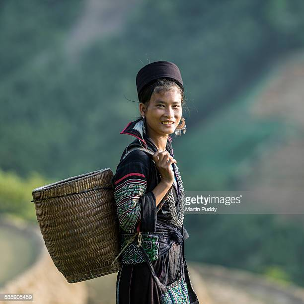 Woman of Black Hmong hill tribe next to rice paddy