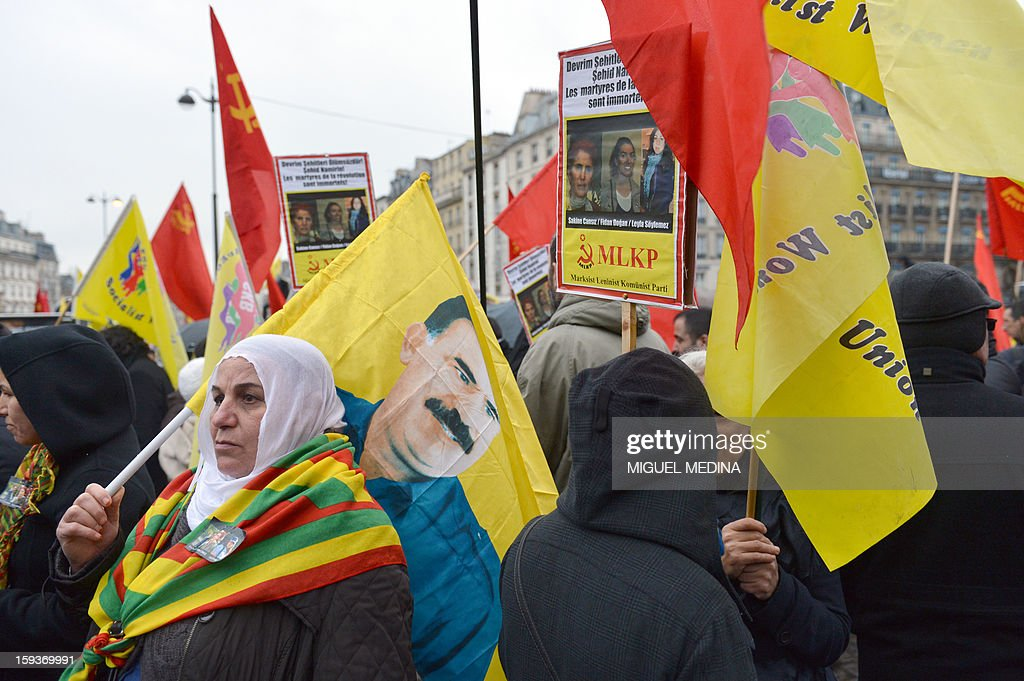 A woman of Kurdish origin (L) holds a flag with the portrait of Kurdish jailed leader of the Kurdistan Workers' Party (PKK), Abdbullah Ocalan, during a demonstration on January 12, 2013 in Paris, two days after the killing of three Kurdish women activists at Paris Kurdistan Information Bureau. Thousands of Kurds from all over Europe are expected in Paris today for what is expected to be an angry protest over the killing of three female activists shot dead at least three times in the head, giving further credence to the theory of an execution-style hit. Kurdish activists have accused Turkey or rogue nationalist elements in the country's military of being behind the killings.