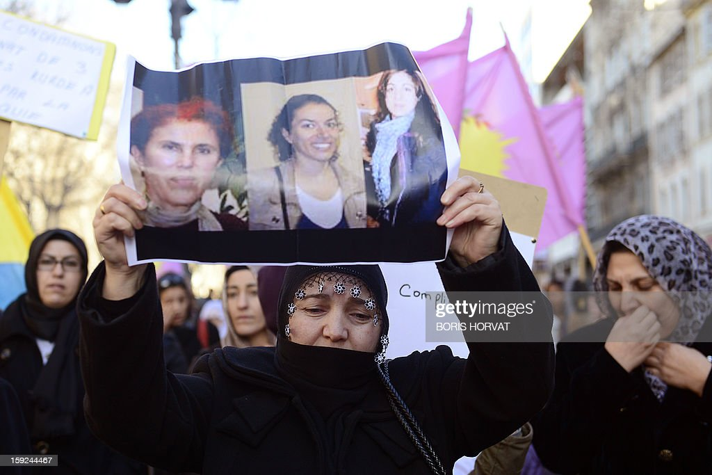 A woman of Kurdish origin holds a poster showing the photos of the three Kurdish women activists killed overnight in Paris during a demonstration on January 10, 2013 in central Marseille. A co-founder of the Kurdistan Workers' Party (PKK) and two other militants were found shot dead on January 10 in Paris, a day after Turkey and the jailed leader of the banned group were reported to have agreed on a peace plan to end a three-decade-old insurgency. AFP PHOTO / BORIS HORVAT