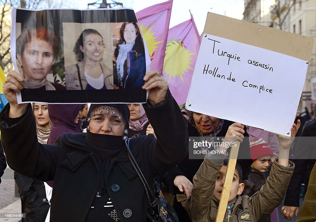 A woman of Kurdish origin holds a poster showing the photos of the three Kurdish women activists killed overnight in Paris next to a boy holding a cardboard reading 'Turkey assassin, Hollande complicit' during a demonstration on January 10, 2013 in central Marseille. A co-founder of the Kurdistan Workers' Party (PKK) and two other militants were found shot dead on January 10 in Paris, a day after Turkey and the jailed leader of the banned group were reported to have agreed on a peace plan to end a three-decade-old insurgency.