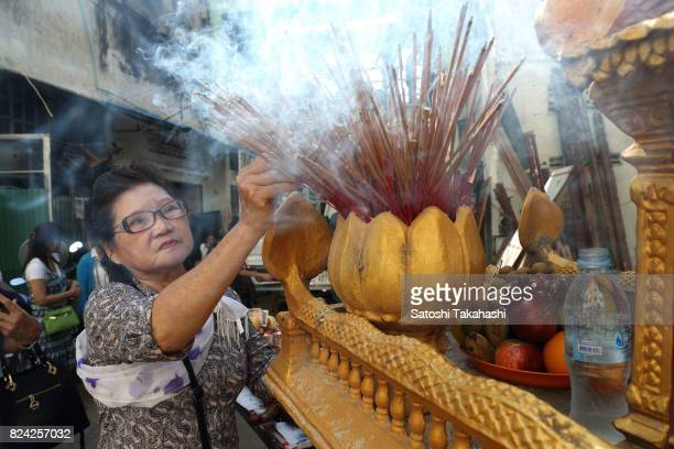 A woman of resident of White Building offers incense sticks to celebrate a farewell ceremony at Phnom Penh's iconic White Building It was built in...
