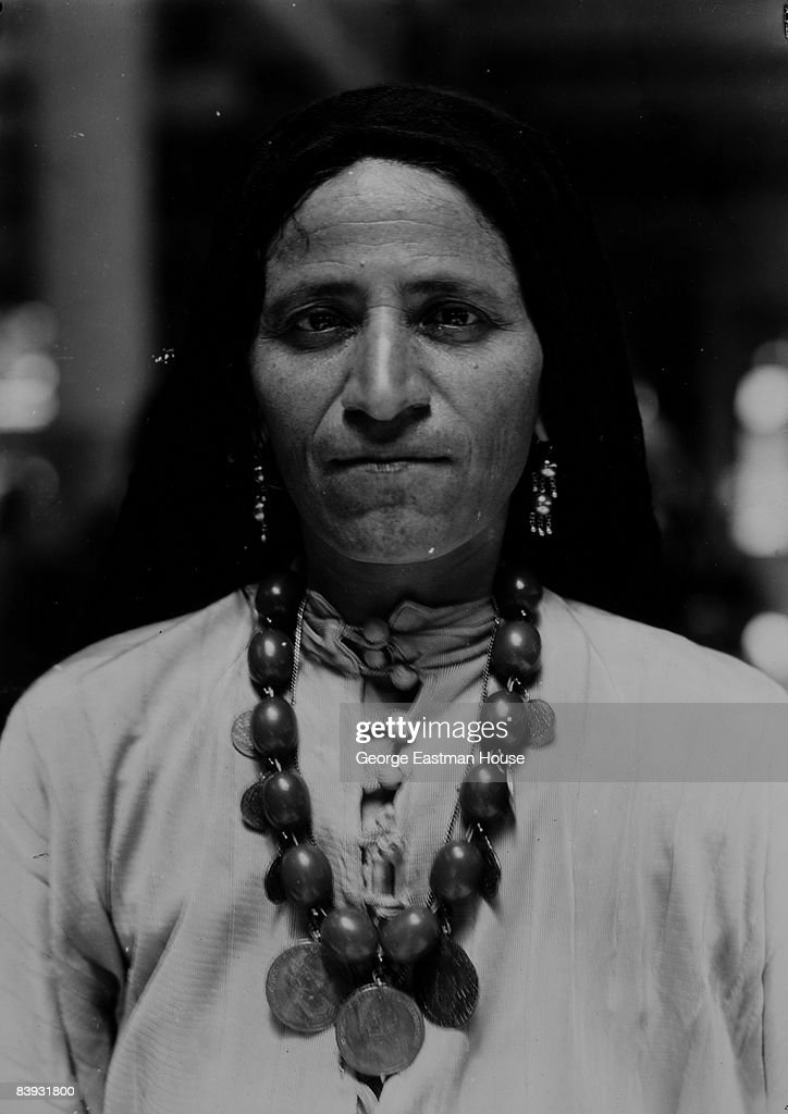 A woman of Syrian-Arab descent wearing amber beads and gold ornaments stands at attention while being processed at Ellis Island. She had tattoo marks on her chin and hands, 1926. New York.