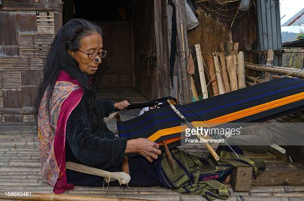 A woman of the Apatani tribe weaving material on a traditional hand loom