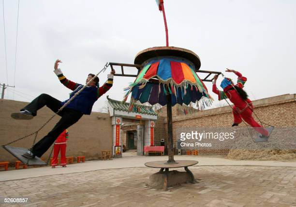 Woman of Tu ethnic minority group play the 'Lunziqiu' one of the nation's traditional sports also known as the 'Swing On the Tire' April 9 2005 in...