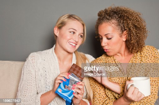 Woman offering friend chocolate