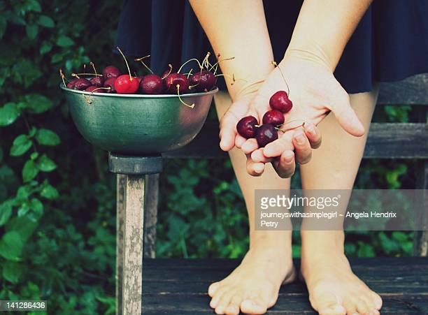 Woman offering handful of cherries.