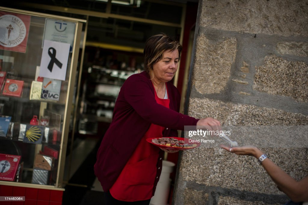 A woman offers chocolates from her sh op to passers by as a poster with a black ribbon on is displayed on the window in memory of the victims of the train crash , on July 26, 2013 in Santiago de Compostela, Spain. The high speed train crashed after it derailed on a bend as it approached the north-western Spanish city of Santiago de Compostela at 8.40pm on July 24th. At least 78 people have died and a further 131 are reported injured. The crash occured on the eve of the Santiago de Compostela Festivities.