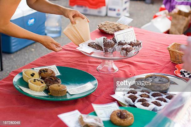 Woman offers fresh pastry at charity fundraiser bake sale