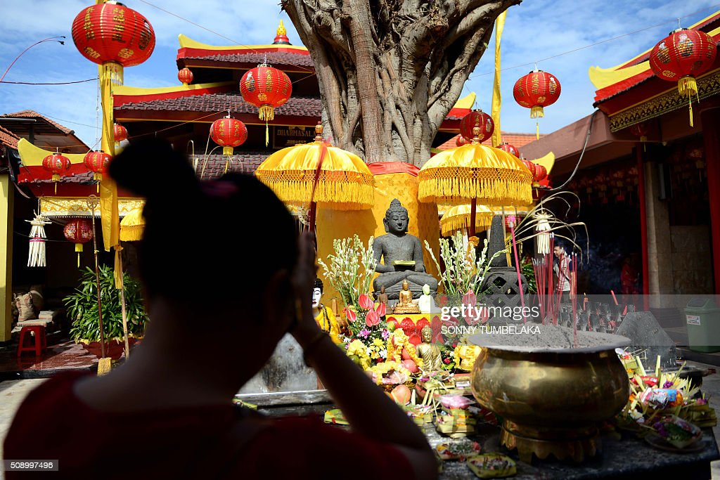A woman offers prayers on the first day of the Lunar New Year of the Monkey at the Dharmayana temple in Kuta, near Denpasar on Indonesia's Bali island on February 8, 2016. The Lunar New Year is celebrated in many parts of the predominantly Muslim country of 250 million people where Chinese heritage took roots through ancient transmigration. AFP PHOTO/SONNY TUMBELAKA / AFP / SONNY TUMBELAKA