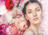 Beautiful young woman on a background of pink flowers. The concept of beauty and health. Beautiful fashion bride, sweet and sensual.
