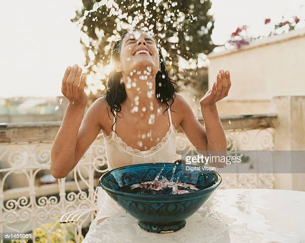 Woman on a Balcony Sits With Her Eyes Close, Splashing Water From a Bowl